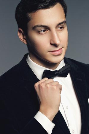 sexualidad: Close-up retrato de hombre joven elegante traje negro, pajarita y camisa en el fondo blanco. Moda modelo estudio de rodaje. Masculinidad y sexualidad. Estilo Lujo.