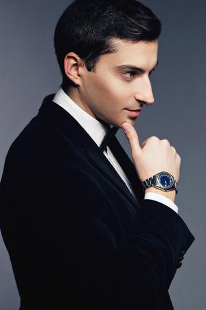 sexualidad: Elegante joven hermoso en juego y camisa blanca con el reloj en el fondo blanco. Moda modelo estudio de rodaje. Perfil cara. Masculinidad y sexualidad. Estilo de negocios de lujo.