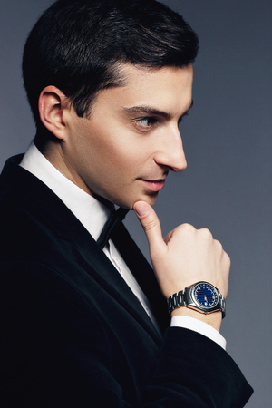 manhood: Close-up portrait of handsome elegant young man in suit and white shirt with watch on white background. Fashion model studio shooting. Profile face. Manhood and sexuality. Luxury business style.