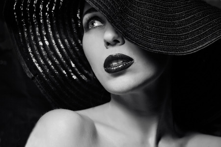 kapelusze: Portret tajemniczej pięknej młodej kobiety o wspaniałej fakturze skóry w czarnym kapeluszu. Modny makijaż glamour mody. Zmysłowe usta. Czarno-biały obraz. Art photo