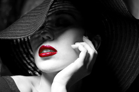 red lips: Portrait of mysterious beautiful young woman with wonderful skin texture  in  black hat. Trendy glamorous fashion makeup. Sensual red lips. Black and white image. Art photo Stock Photo
