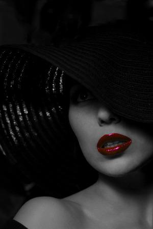 Portret van mysterieuze mooie jonge vrouw op zoek in de verte met prachtige huid textuur in zwarte hoed. Trendy glamoureuze fashion make-up. Sensuele rode lippen. Zwart-wit beeld. Kunst foto.