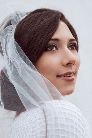 smoky eyes: Closeup portrait of bride beautiful young woman in white veil and dress. Wedding photo. Romantic style. Happiness. Wedding fashion makeup light smoky eyes  pearly beige and brown shades. Stock Photo