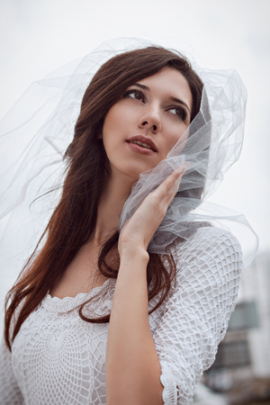 smoky eyes: Portrait of bride beautiful young woman in white veil and dress. Wedding photo. Romantic style. Happiness. Wedding fashion makeup light smoky eyes pearly beige and brown shades.