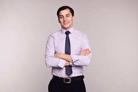 belleza masculina: Confiado exitoso hombre joven hermoso sonriente hombre de negocios en pantalones cl�sicos negro, camisa blanca y corbata en fondo gris. Virilidad. Belleza masculina. Modelo de manera tiro del estudio. Estilo italiano. Lujo.
