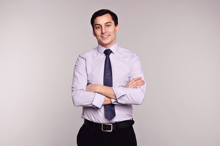 manhood: Confident successful young handsome smiling man businessman in black classic pants, white shirt and tie on grey background. Manhood. Male beauty. Fashion model studio shot. Italian style. Luxury.