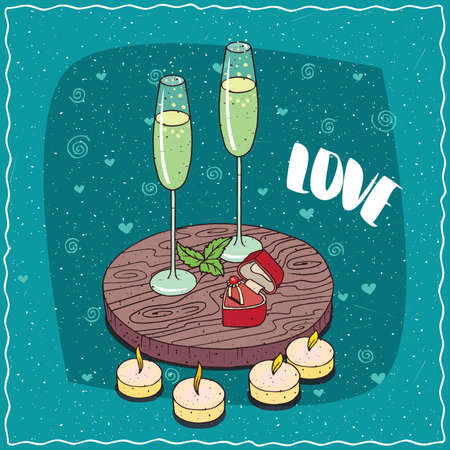 Romantic composition on wooden board, glasses of champagne or cider and wedding ring in box in the shape of heart. Next candles.