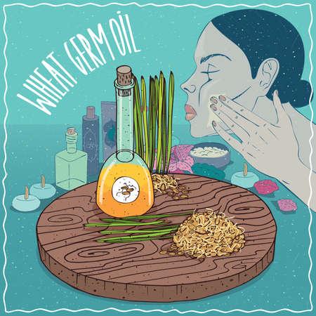 ガラスのデカンターの小麦胚芽油や穀物細菌。女の子の顔に顔のマスクを適用します。スキンケアのために使用される自然の植物油