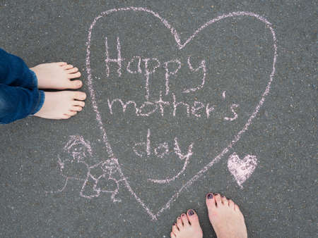 familiy: Mothers day - heart shape chalk drawing and the feet of a child and of a woman