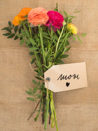 Beautiful bouquet of flowers with a message I love mom on jute fabrics Stock Photo