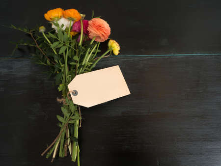 textfield: Beautiful bouquet of flowers and blank textfield with copyspace on a dark wooden background Stock Photo