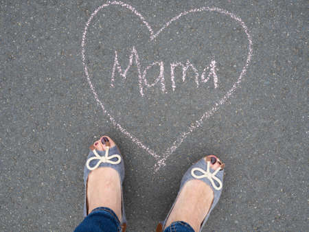 mama: Mothers day - heart shape chalk drawing and the feet of a mother with the german text message mama Stock Photo