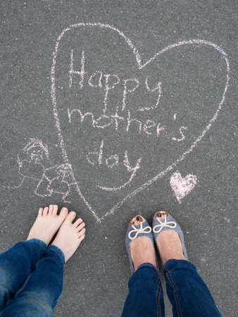 familiy: Mothers day - heart shape chalk drawing and the feet of a boy and the feet of his mother