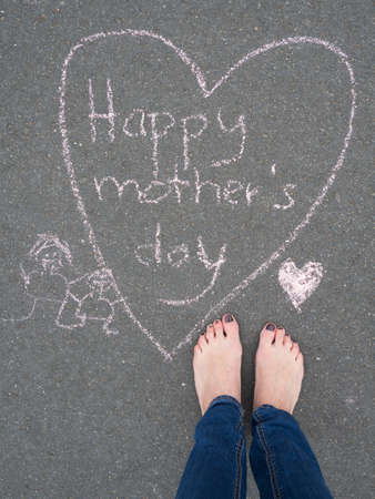 familiy: Mothers day - heart shape chalk drawing and the feet of a woman on the asphalt ground