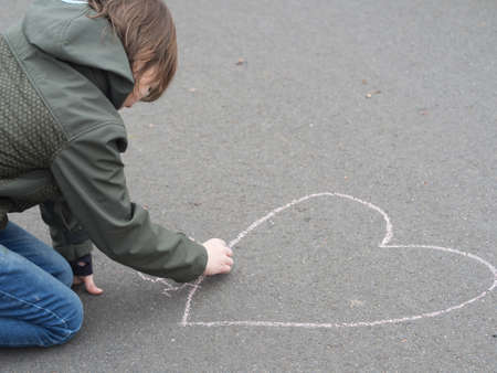 facing away: Little boy draws a heart shape with chalk on the ground Stock Photo