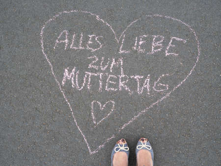 Liebe: Mothers day - heart shape chalk drawing and the feet of a mother with the german text message - Alles Liebe zum Muttertag Stock Photo