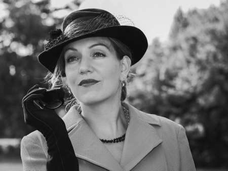 30 something women: Vintage black and white portrait of a woman with a suit and a black hat looking dreamily Stock Photo