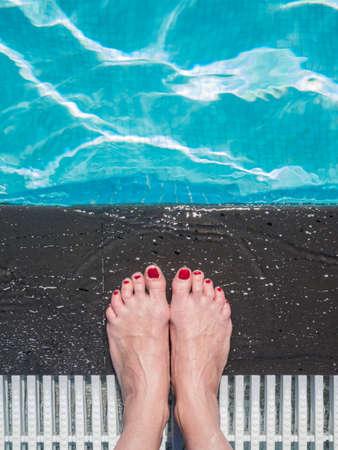 femal: Beautiful femal feet with red nail polish at the swimming pool