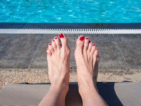 lounge chair: Feet of a woman lying in a lounge chair by the pool