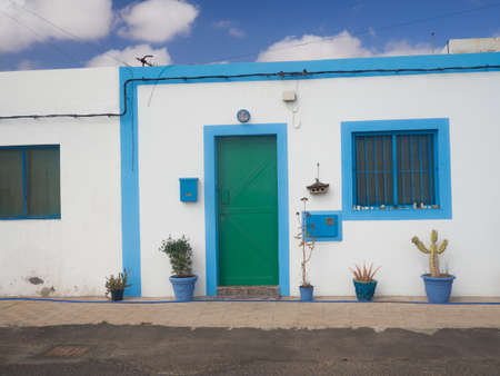 southern european: Beautiful spanish white house with a green door and a blue sk