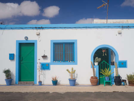 house with style: Beautiful spanish white house with a green door and a blue sky