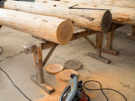 woodcutting: wood logs on wooden trestles. Some slices are on the ground