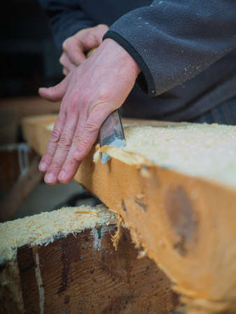 woodcutting: Carpenter is planing down a wooden board with a crowbar