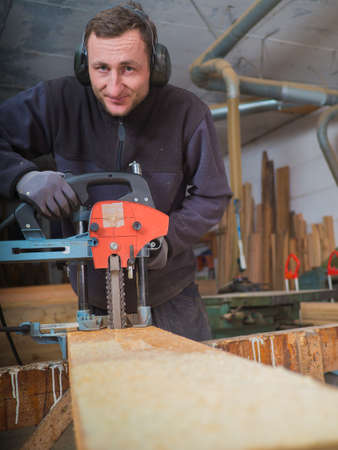 smilie: Close up of a smiling Carpenter who is mill-cutting a wooden board with chain mortiser. He is wearing soundproofing headphones