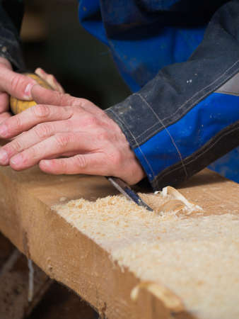 crowbar: Carpenter is planing down a wooden board with a crowbar