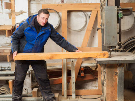 woodcutting: Carpenter with a plank on an electric saw machine