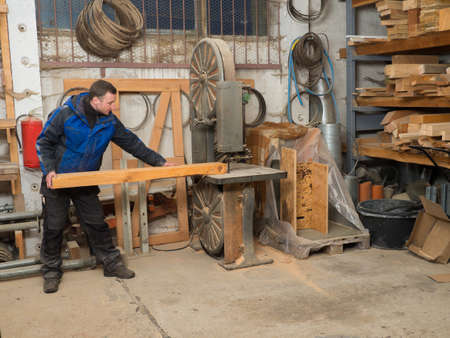 woodcutting: Carpenter workshop. He is holding a plank on an electric saw machine Stock Photo