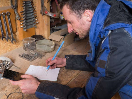 earnestly: Portrait of a carpenter with tablet working on blueprint  in his workshop Stock Photo