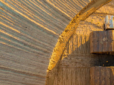 top view of the sand pit. photo from a career tractor. yellow sand at sunset. sand with drawings. picture for the background.