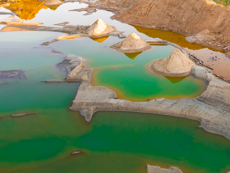A view from above on a sandy quarry filled with water. photo from a drone. water is green. yellow sand at sunset. picture for the background. Stockfoto