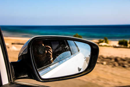 photographer in the mirror of a car