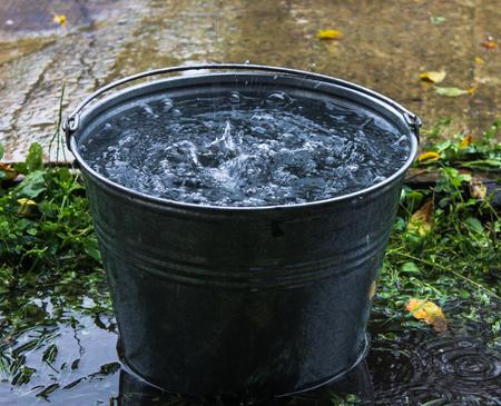 屋根から滴り落ちる水。水の入ったバケツ。雨
