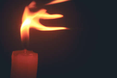 photo of a candle flame swaying in the wind against a black background