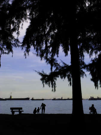 Silhouette of a  of three at the East Coast Park and a handicapped in wheel chair.