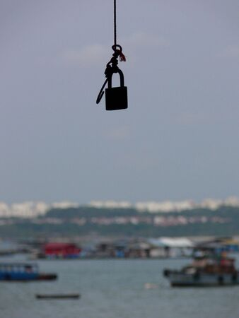 Lock hanging from tree.  Looks like you need a key to enter into the travel world. photo