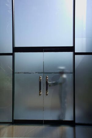 Doorman waiting to open doors at a hotel photo