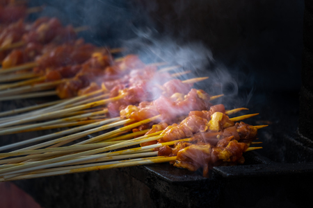 Satay being grilled with smoke and yummy looking. Satay is very popular hawker and restaurent dish as it is very delicious and very popular in Malaysia and Indonesia. Archivio Fotografico