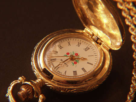 an antique gold pocket watch with flowers painting in the center and Roman digits, gold chain and decoration  photo