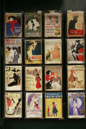 colourful images: display of Art Nouveau postcards on a dark wall , postcards are incased and in rows of four by four