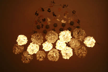 sponged: view of sixteen flower shaped grouped hanging ceiling light fixtures with a brown background,
