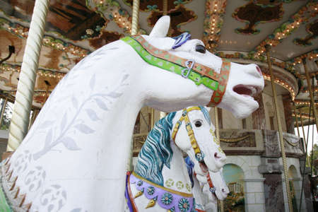 close up ,  side view of a vintage carousel interior with three white colorfully painted horses  photo