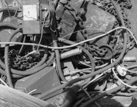 intertwined: a mass of wires , cables , pipes , chains and boxes intertwined , old , dirty and rusty