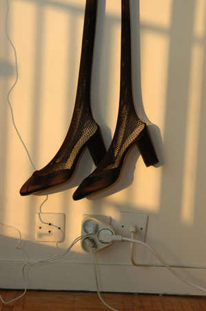 intriguing: surreal interpretation of dangling shoes against a wall