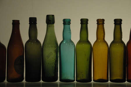 a row of similarly shaped colored glass bottles, with shadows over white background photo