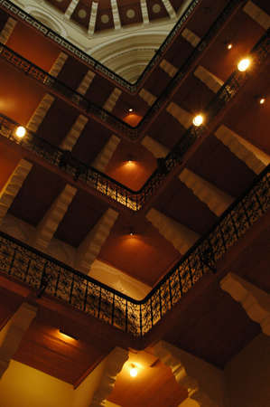 latticework: view from inside a building, in the corner, looking up at four stories of wood-floored balconies, with iron latticework railings, below a domed ceiling with designed off-white molding Stock Photo
