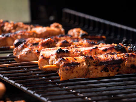 Close shot of chicken kebabs cooking on a barbecue. Фото со стока
